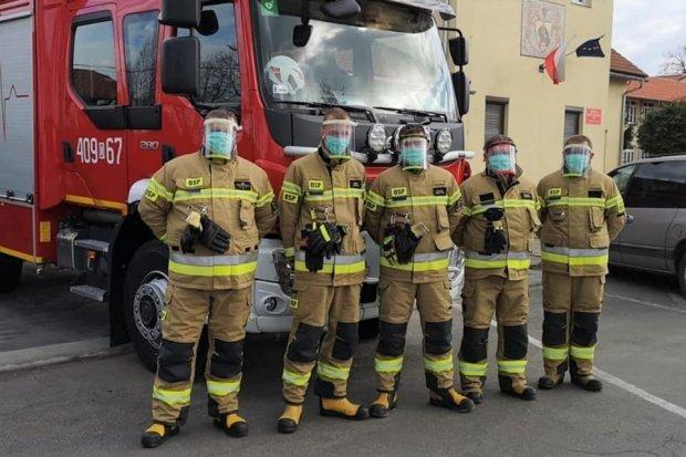 Strażacy i policjanci z Warty z przyłbicami ochronnymi