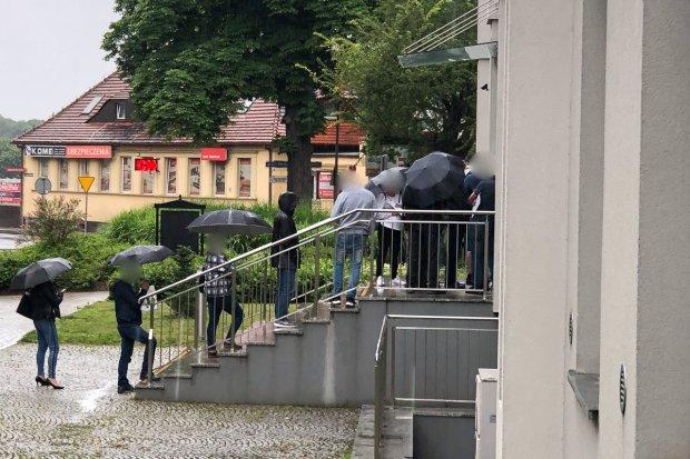 """Długa kolejka przed Starostwem. Ludzie stoją w deszczu. """"Jak śledzie"""""""