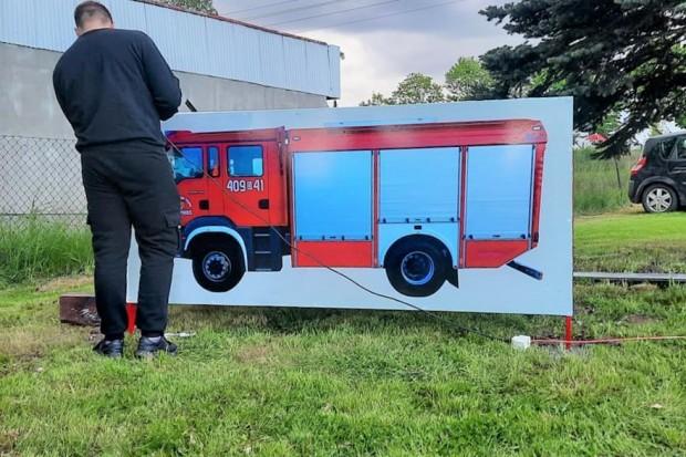 Minisamochód strażacki koło remizy w Różyńcu. Druhowie pomagają potrzebującym dzieciom