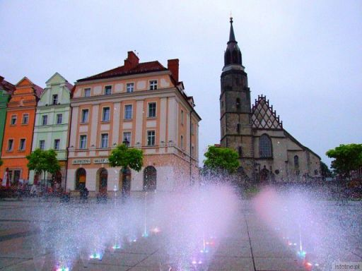 Rynek, bazylika i fontanna w deszczowy dzień.