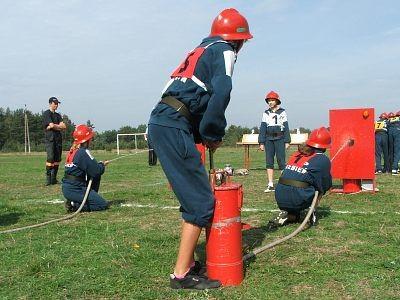 Dziewczyny rywalizują w konkurencji trafianie strumieniem wody d