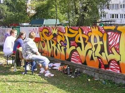 Modzi ludzie oglądaja grafitti na murze