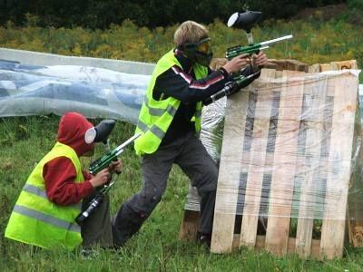 Chłopcy chowają się za drewnianą paletą