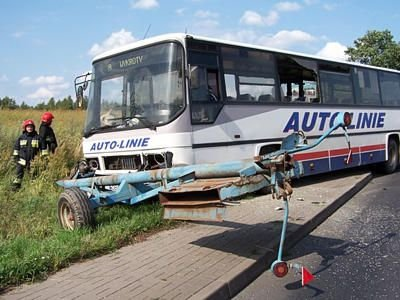 Strażacy i autobus po zderzeniu z ciągnikiem rolniczym