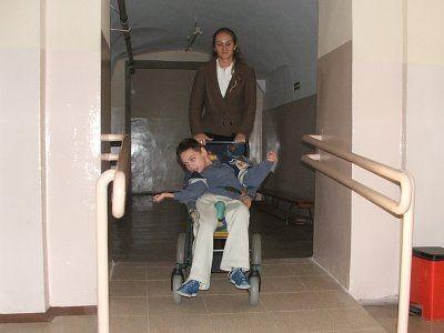 Kobieta sprowadza po podjeździe wózek z niepełnosprawnym chłopcem