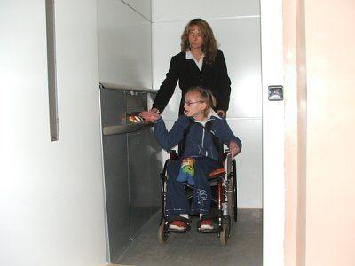 Kobieta i niepełnosprawna dziewczynka na wózku inwalidzkim wewnątrz windy
