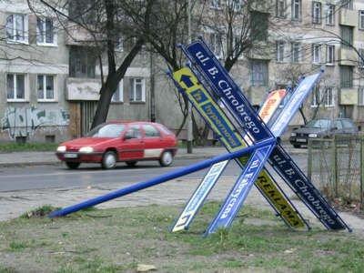 Przewrócony słup z nazwami ulic przy skrzyżowaniu
