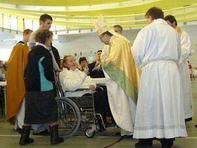 Biskup przyjmuje dary od kobiety na wózku inwalidzkim