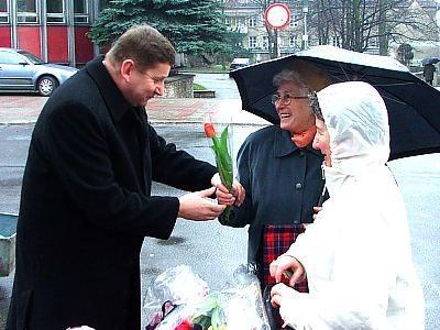 Kazimierz Sas wręcza kobietom tulipany