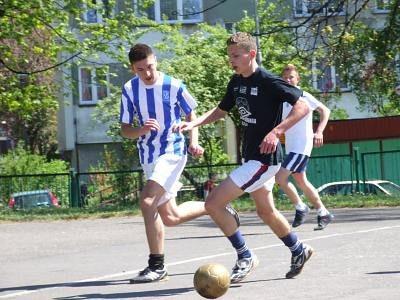 Dwóch piłkarzy na asfaltowym boisku