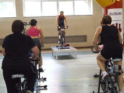 Kobiety na rowerach stacjonarnych i prowadzący zawody