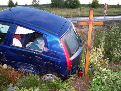 Samochód osobowy obok drewnianego krzyża