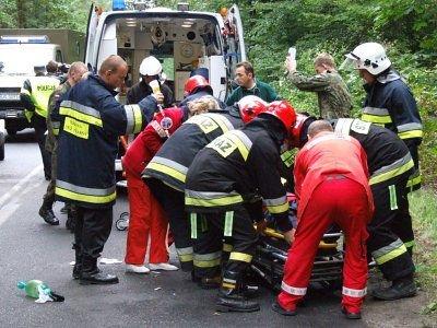 Strażacy i pracownicy pogotowia przenoszą rannego na nosze