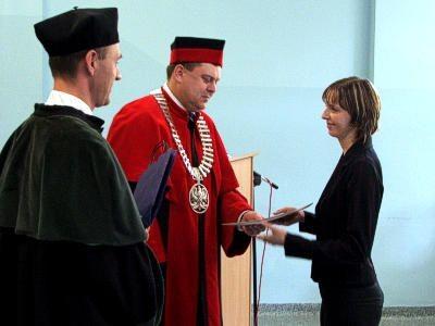 Władze uczelni wręczają list gratulacyjny jednej ze studentek