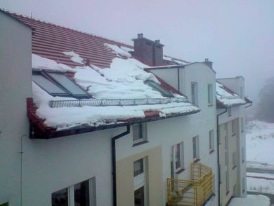 Śnieg zalegający na dachu budynku przy ulicy Śluzowej