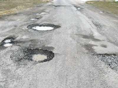 Dziury na drodze prowadzącej do strefy przemysłowej w Wykrotach