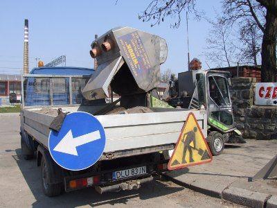 Kierowca zamiatarki opróżnia pojemnik z piachem zebranym z ulicy