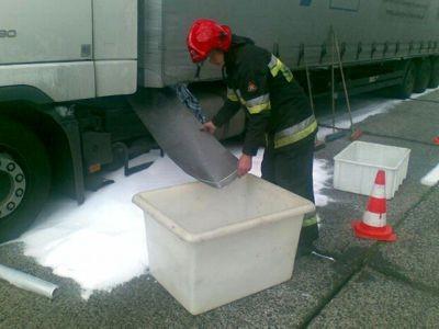 Strażak zsypuje granulat do zbiornika