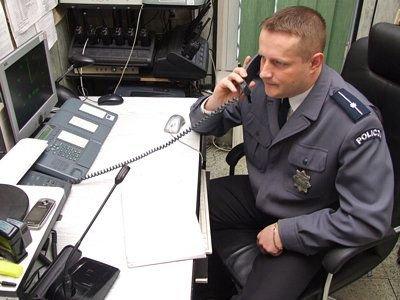 Młodszy aspirant Krzysztof Policht przy telefonie alarmowym 997
