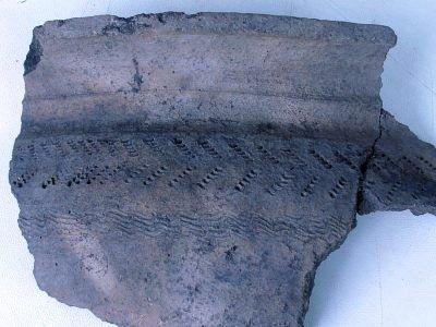 Naczynie gliniane wykopane podczas prac archeologicznych z charakterystycznym wzorem (nakłucia wykonane grzebykiem)