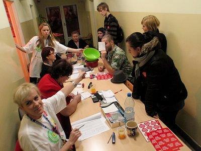 Kilka osób na bieżąco liczyło pieniądze przynoszone przez wolontariuszy