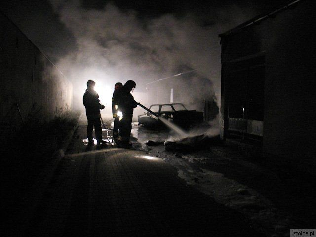 Strażacy gaszą opony leżące przy budynku