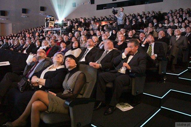Uczestnicy gali oglądają prezentację na ścianie kina. W drugim rzędzie prezydent Piotr Roman.