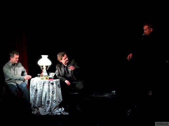 Mirosław Baka śpiewa w cieniu, kiedy Kasprowicz z widzem piją wódkę w takt piosenki, zakąszając ogórkami kiszonymi
