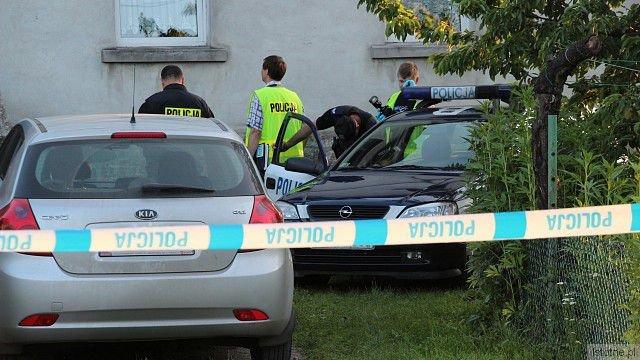 Policjanci przed budynkiem, gdzie znaleziono zwłoki kobiety