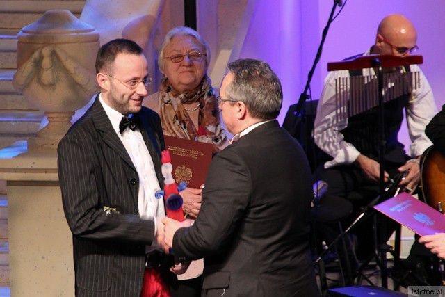Krzysztof Gwizdała odbiera nagrodę z rąk prezydenta Piotra Romana