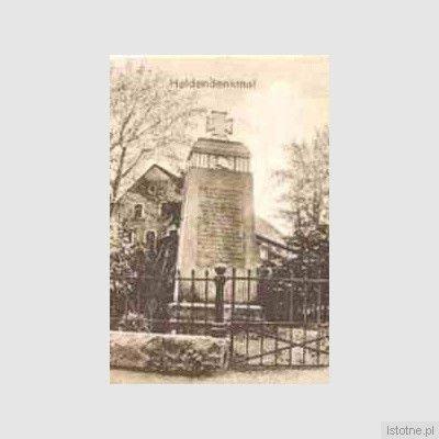 Pomnik poległych żołnierzy na cmentarzu z zabudowaniami w tle
