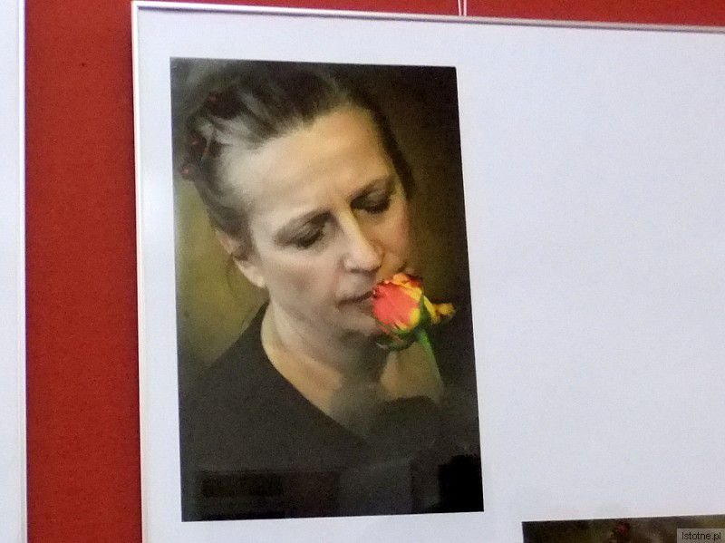 """Portret """"Róży z różą"""" Bożeny Gałan niesie w sobie obraz kobiecego losu, który bywa trudny, bolesny, naznaczony licznymi bliznami po razach, jakie rozdało życie, losu z którym bohaterka na zdjęciu pogodziła się, ale choć ją naznaczył, to jej nie pokonał."""