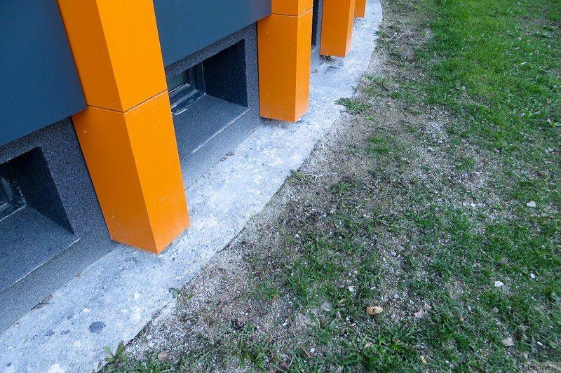 Zabrudzony cokół wokół budynku i wydeptana trawa.