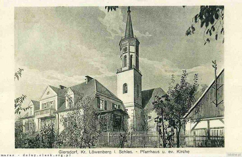 Zdjęcie wykonano w latach 40. XX wieku. Prezentuje dom pastora oraz kościół