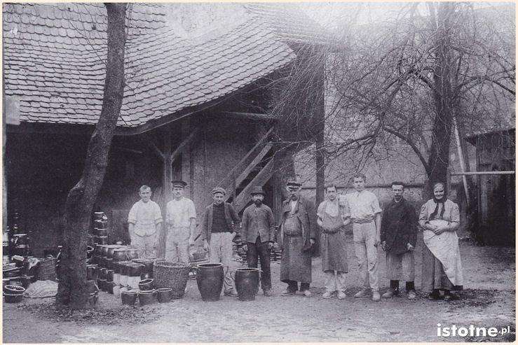 Zdjęcie z 1909 roku ukazujące ludzi na tle brązowych garnków