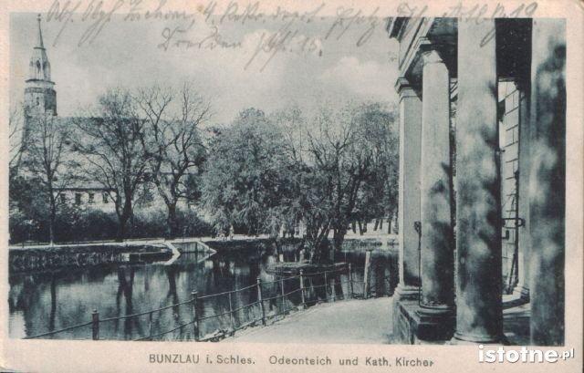 Po prawej stronie pocztówki fragment wejścia do budynku z widokiem na staw i kościół