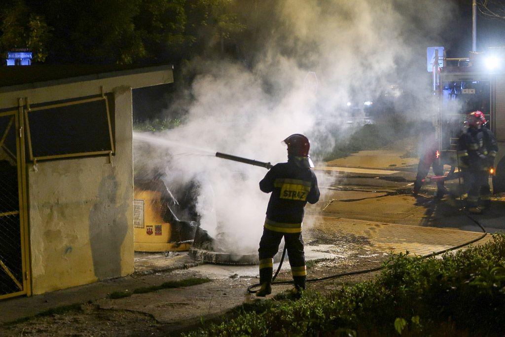 Strażak gasi płonący pojemnik na śmieci