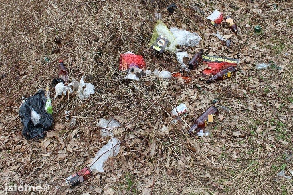 Odchody, puszki i butelki na terenach zielonych za Dino