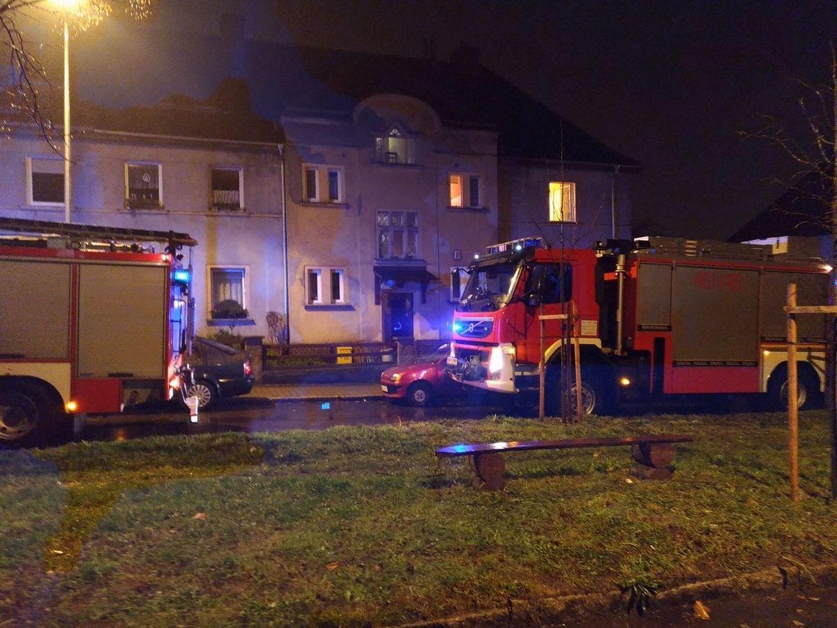 Wozy straży pożarnej przed domem na Okrzei