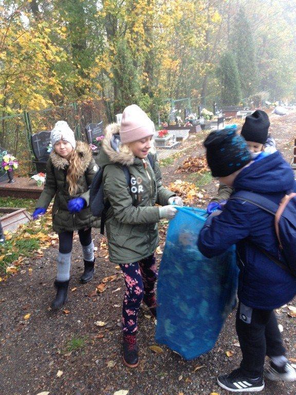 Uczniowie szkoły podstawowej nr 5 sprzątają cmentarz