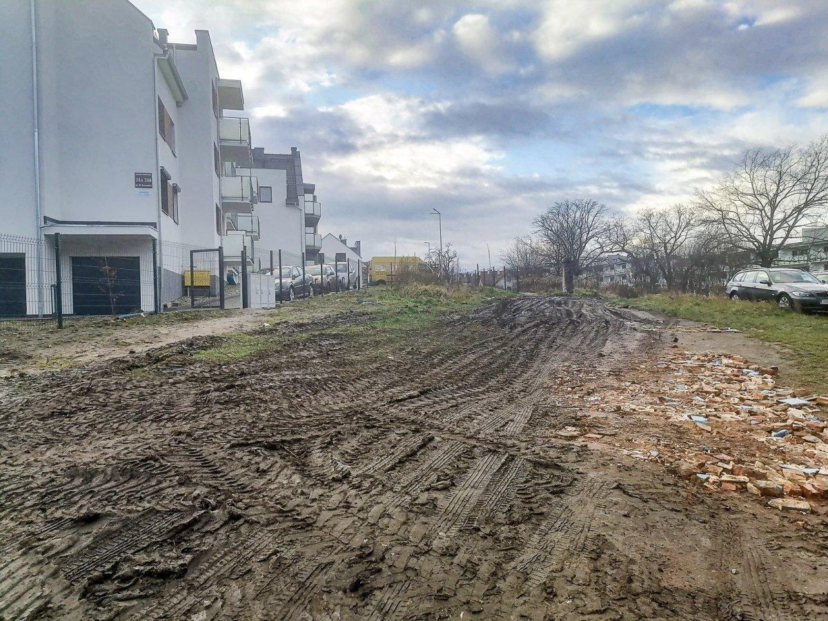 Rozjechana droga między budynkami przy ul. Reymonta i Garncarskiej