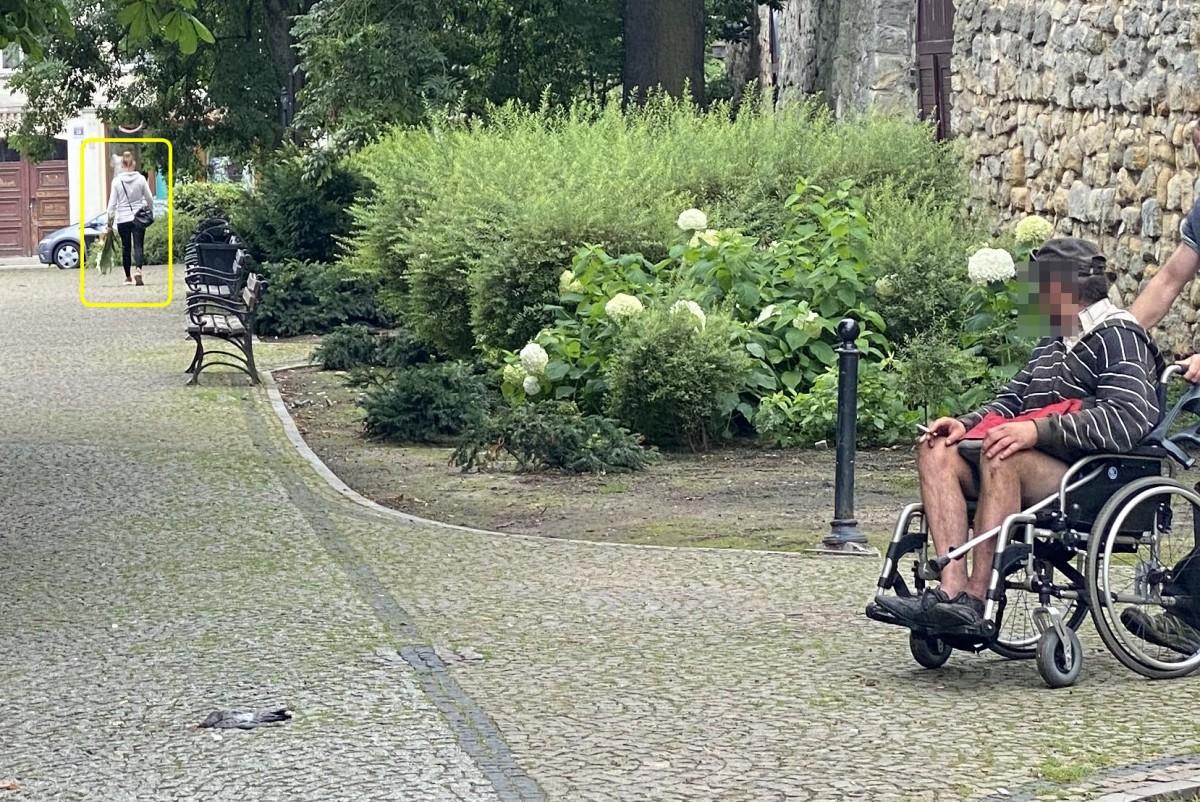 Kobieta odchodząca z kwiatami spod pomniku PW