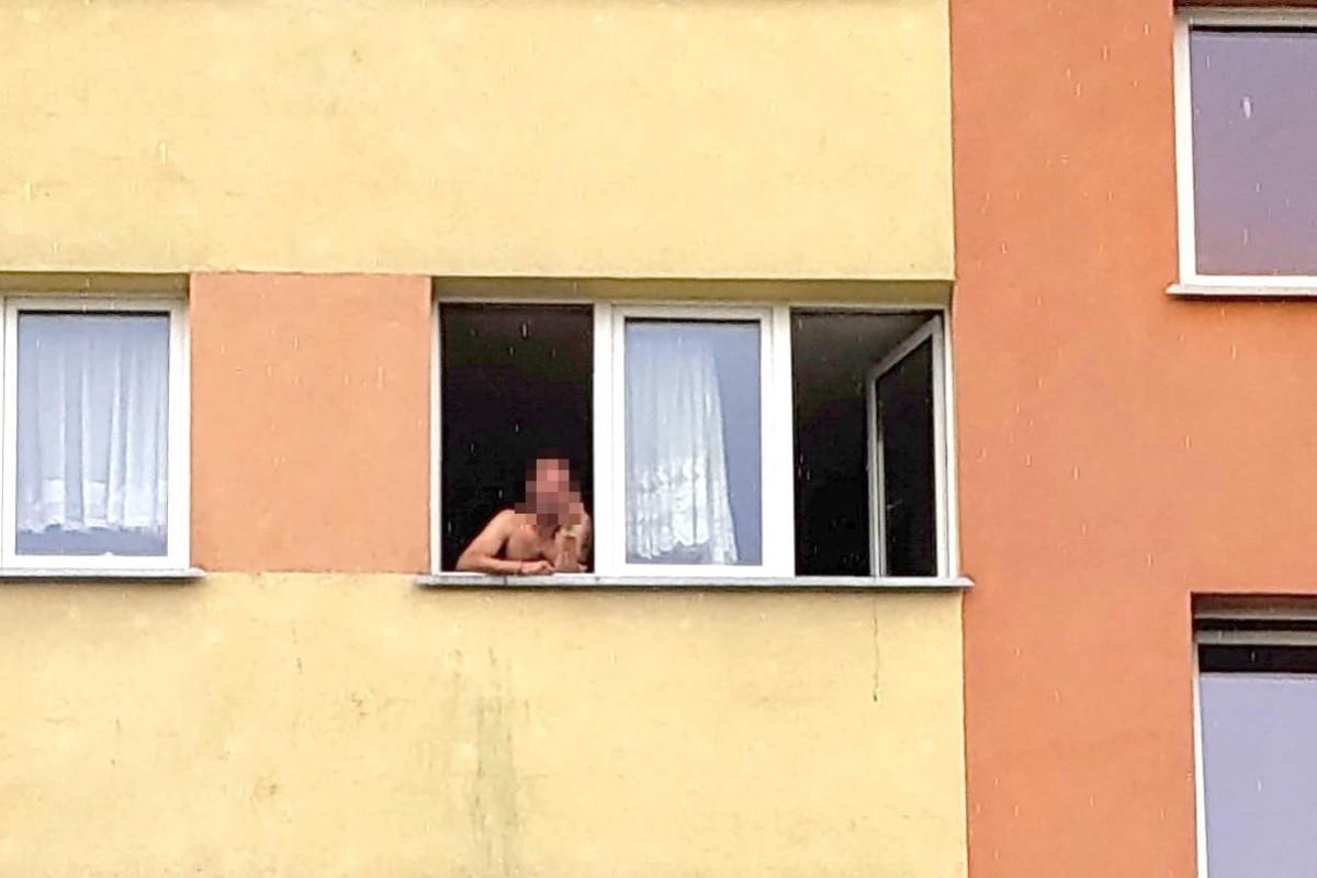 Mężczyzna w oknie mieszkania na 3 piętrze