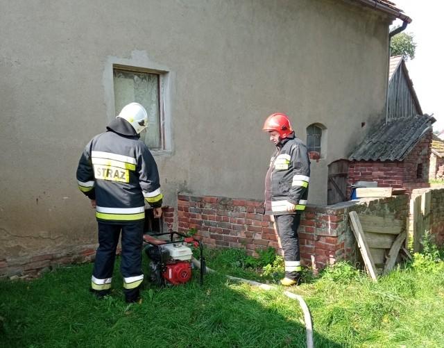 Strażacy z OSP Wierzbowa - wypompowywanie wody z zalanego budynku